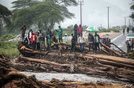 People stand on debris blockinag a highway after River Muruny burst its bank following heavy rains in Parua village, about 85 km…