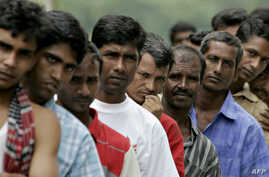 FILE - Bangladeshi migrant workers wait in line for food donated by a goodwill charity group for Christmas outside the Bangladeshi High Commission in Kuala Lumpur, Malaysia, Dec. 25, 2007.