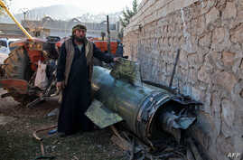 A man stands next to a fragment of a ground-to-ground missile fired by government forces that hit a makeshift camp in the village of Qah near the Turkish border in northwestern Idlib province, Syria, killing 15 civilians, including six children.