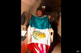 This photo released by by Mexico's Foreign Minister Marcelo Ebrard shows Bolivia's former President Evo Morales holding a Mexican flag aboard a Mexican Air Force aircraft, Nov. 11, 2019.