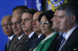 Brazil's President Jair Bolsonaro, center, and his ministers attend the launch of the Green and Yellow program to create formal jobs for young people, at the Planalto Presidential Palace, in Brasilia, Brazil, Nov. 11, 2019.