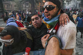 An injured anti-government demonstrator is carried to safety during clashes with the Chilean police in Santiago, Chile, Nov. 12, 2019.