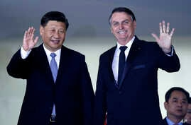 China's President Xi Jinping, left, and Brazil's President Jair Bolsonaro wave to reporters upon Xi's arrival for a bilateral meeting on the sidelines of the 11th BRICS Summit, at Itamaraty Palace, in Brasilia, Brazil, Nov. 13, 2019.