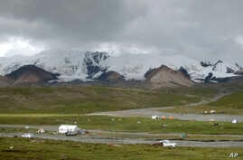FILE - Pilgrims and herders camp at the foot of the holy Tibetan mountain range Amnye Machen on the eastern edge of the Tibetan Plateau in northwestern China's Qinghai Province, Aug. 20, 2018.