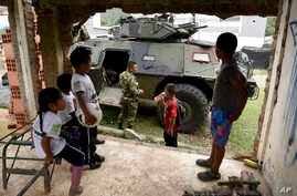 Children look at an armored vehicle in Toribio, southwest Colombia, Oct. 30, 2019.