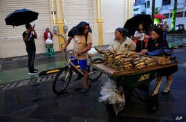 A man on a bike stops to buy plantains from a vendor in San Salvador, El Salvador, Aug. 20, 2018.