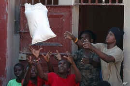 Men catch a bag of rice as they unload a government food distribution, in a small section of the Delmas neighborhood where over…