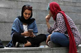 FILE - A woman checks her cell phone sitting with a companion on the steps outside a shopping mall in northern Tehran, Iran, July 2, 2019.