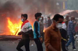 Anti-government protesters set fires and close streets during ongoing protests in Baghdad, Iraq, Nov. 9, 2019.