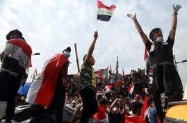 Anti-government protesters stand on barriers set up  by Iraqi security forces, Baghdad
