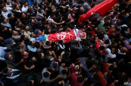 Palestinian mourners carry the body of Omar Badawi, 22, during his funeral at the al-Arroub refugee camp in the West Bank city of Hebron, Nov. 11, 2019.