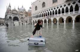 A tourist pushes her floating luggage in a flooded St. Mark's Square, in Venice, Italy, Nov. 13, 2019.