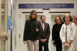 First lady Melania Trump, left, accompanied by U.S. Secretary of Health and Human Services Alex Azar, walks with staff during a visit to Boston Medical Center, in Boston, Massachusetts, Nov. 6, 2019.