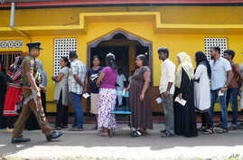 Sri Lankans queue to cast their votes as a police officer stands guard at a polling station during the presidential election in Colombo, Sri Lanka, Nov. 16, 2019.