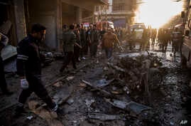 People check the aftermath of a car bomb blast in the city of Qamishli, northern Syria, Nov. 12, 2019.