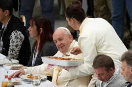 Pope Francis sits at a table during a lunch, in the Paul VI Hall at the Vatican, Nov. 17, 2019.