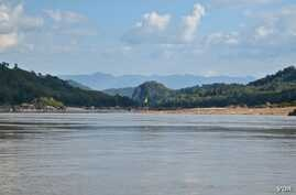 A yellow flag marks the site on the Mekong River in northern Laos where the government plans to build the Luang Prabang hydropower dam.