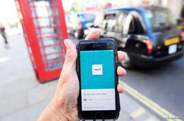 FILE - A photo illustration shows a London taxi passing as the Uber app logo is displayed on a mobile phone, as it is held up for a posed photograph in central London, Britain, Sept. 22, 2017.