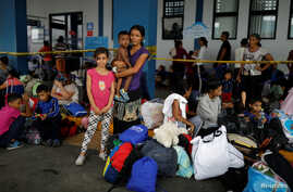 FILE - A Venezuelan migrant woman poses for a picture with her children, while they wait to have their documents processed at the Ecuador-Peru border, on the outskirts of Tumbes, Peru, June 17, 2019.