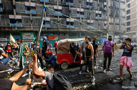A demonstrator uses a slingshot during ongoing anti-government protests in Baghdad, Iraq.