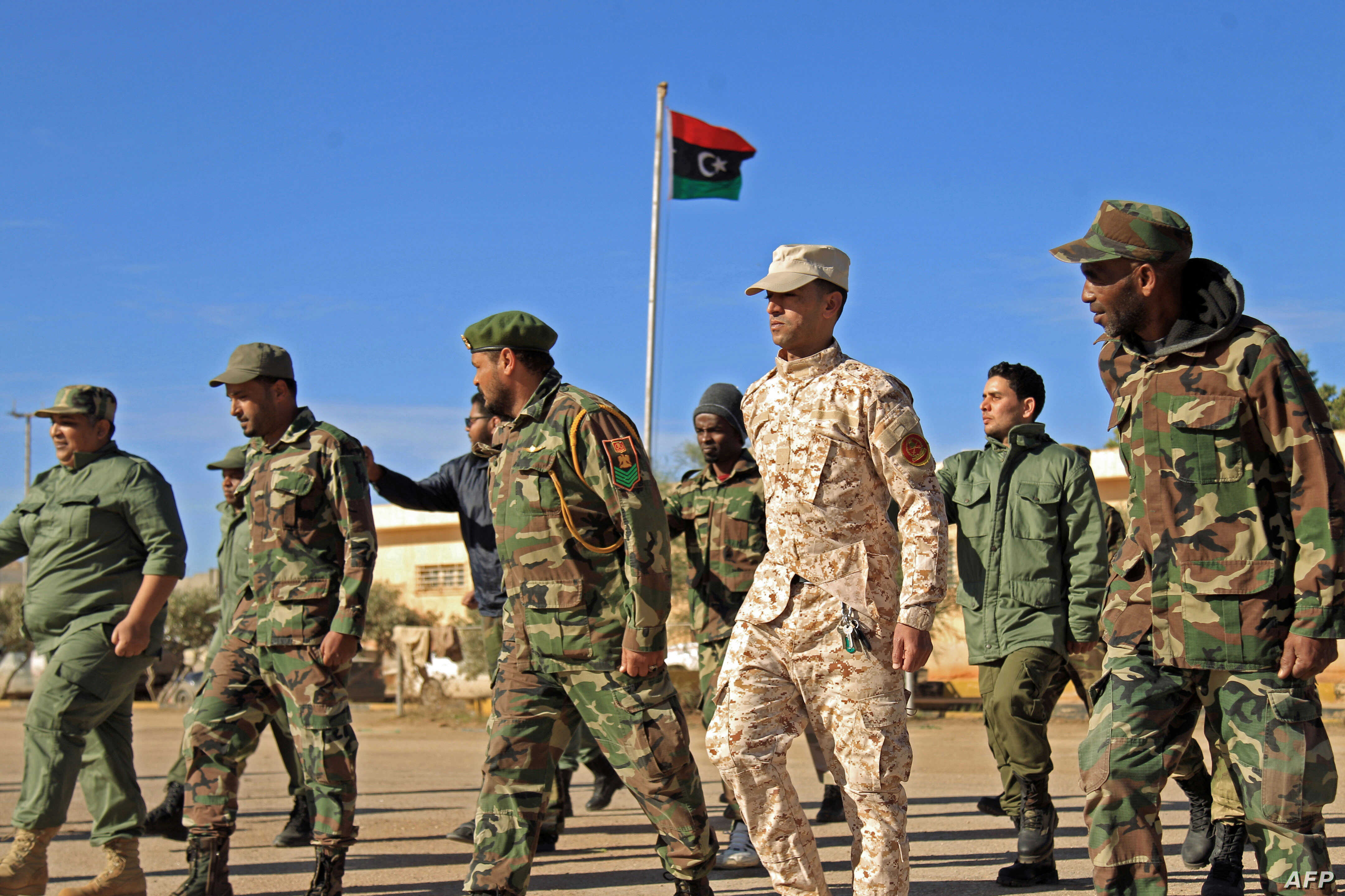 Fighters of a military battalion loyal to Libyan General Khalifa Haftar march during the morning assembly in the eastern city…