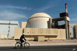 FILE - In this Oct. 26, 2010 file photograph, a worker rides a bicycle in front of the reactor building of the Bushehr nuclear…