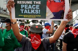 Masked members of the outlawed National Democratic Front of the Philippines, the umbrella organization of the Philippine communist movement, hold a sign during a demonstration in Manila, Philippines, March 25, 2019.