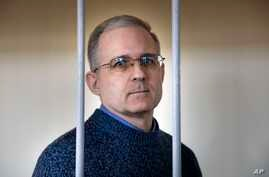 FILE - Paul Whelan, a former U.S. marine, who was arrested for alleged spying in Moscow at the end of 2018, stands in a cage while waiting for a hearing in a court room in Moscow, Russia, Aug. 23, 2019.