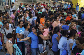 """In this Aug. 30, 2019, photo, migrants, many who were returned to Mexico under the Trump administration's """"Remain in Mexico,""""…"""