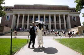FILE - In this July 16, 2019, file photo, people stop to record images of Widener Library on the campus of Harvard University…