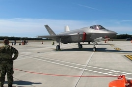 FILE - In this Sept. 19, 2019 file photo, National Guard members, left, view the first two F-35 fighter jets that arrived at…