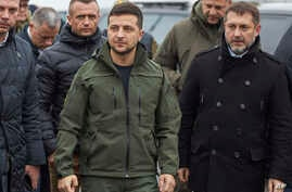 Ukrainian President Volodymyr Zelenskiy, center, visits reconstruction of the bridge crossing over the Siverskyi Donets River, where the local residents cross the delimitation line in Stanitsa village, Luhanska in eastern Ukraine
