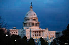 FILE - In this Tuesday, Nov. 12, 2019, file photo, the U.S. Capitol is seen as the sun sets in Washington. Negotiations on a…