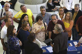 FILE - People inquire about temporary positions available for the 2020 Census during a job fair designed for people fifty years or older in Miami, Sept. 18, 2019. On Friday, Dec. 6, the U.S. government issues the November jobs report.