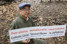 Katsumi Takenaka holds a protesting banner during an interview with The Associated Press in Tokyo, Dec. 10, 2019.