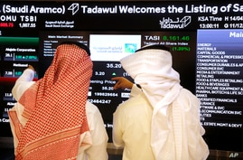Saudi stock market officials watch the market screen displaying Saudi Arabia's state-owned oil company Aramco after the debut of Aramco's initial public offering (IPO) on the Riyadh's stock market in Riyadh, Saudi Arabia, Dec. 11, 2019.