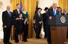 President Donald Trump with, from left, Vice President Mike Pence, Jared Kushner and Ivanka Trump and their children