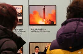 Visitors watch a photo showing North Korea's missile launch at the Unification Observation Post in Paju, South Korea, near the…
