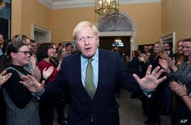 Britain's Prime Minister Boris Johnson is greeted by staff as he returns to 10 Downing Street, London.