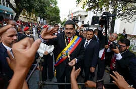 Venezuela's President Nicolas Maduro, center, greets supporters as he arrives at the National Constituent Assembly's building…