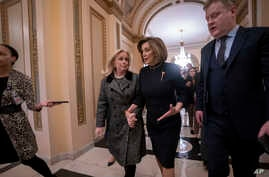 Speaker of the House Nancy Pelosi, D-Calif., holds hands with Rep. Debbie Dingell, D-Mich., at the Capitol in Washington, Dec. 18, 2019.