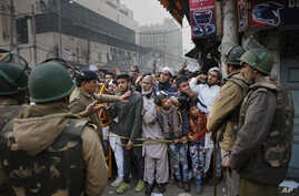 Indian policemen stop protesters at a police barricade in New Delhi, India, Friday, Dec. 20, 2019. Police banned public…