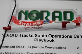 A pen rests on the playbook for volunteers who will be taking calls from around the globe in the NORAD Tracks Santa center at Petserson Air Force Base, Dec. 23, 2019, in Colorado Springs, Colo.