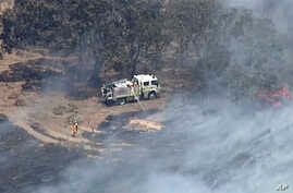 In this image made from video, an aerial scene shows firefighters extinguishing wildfires in the Adelaide Hills, Australia, Dec. 24, 2019.