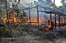 A Maungda hut burning in Western Myanmar. (Photo: Steve Sandford / VOA)