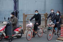 People on bicycles and electric scooters wear masks as they wait at a traffic light after a yellow alert was issued for smog in…