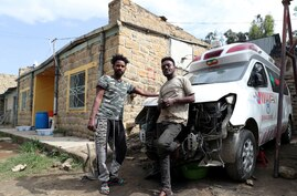 Eritrean nationals Goitom Tesfaye (L), 24 and Filimon Daniel (R), 23, pose for picture in their garage in Mekele, Tigray Region…