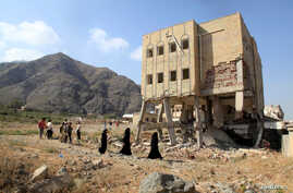 FILE PHOTO: People walk past a school damaged during the ongoing war in Taiz, Yemen, December 18, 2018. REUTERS/Anees Mahyoub…