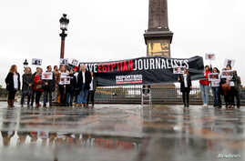 Reporters Without Borders (RSF) activists demonstrate in front of the Louxor's Obelisque on the Place de la Concorde square in…
