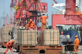 Workers load goods for export onto a crane at a port in Lianyungang, Jiangsu province, China June 7, 2019. Picture taken June 7…
